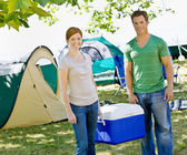 Couple carrying cooler at campsite — Stock Photo