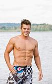 Man in swim trunks wading in lake — Stock Photo
