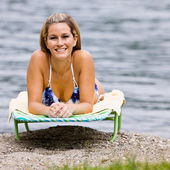 Woman laying on lounge chair at beach — Stock Photo