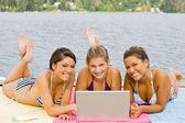 Amici posa sul molo con il computer portatile — Foto Stock