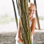 Girl hiding behind tree — Stock Photo