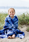 Girl wrapped in blanket at beach — Stock Photo