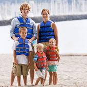 семья носить куртки жизни на пляже — Стоковое фото