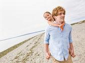 Vader geven dochter piggy terug rit op strand — Stockfoto