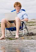 Kumsalda dizüstü kullanan adam — Stok fotoğraf
