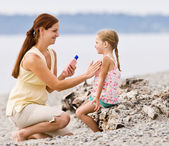 Mother applying sunscreen to daughter at beach — Stock Photo