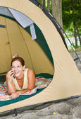 Woman laying in tent using cell phone — Stock Photo