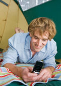 Man in tent text messaging on cell phone — Stock Photo