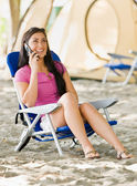 Woman talking on cell phone at campsite — Stock Photo