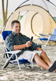 Man text messaging on cell phone at campsite — Stock Photo