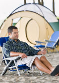 Man using mp3 player at campsite — Stockfoto