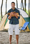 Man carrying wood at campsite — Stock Photo