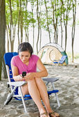 Woman text messaging on cell phone at campsite — Stock Photo