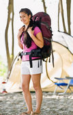 Woman carrying backpack at campsite — Stock Photo
