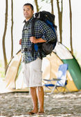 Man carrying backpack at campsite — Stock Photo