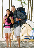 Couple carrying backpacks at campsite — Stock Photo