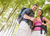 Couple in backpacks looking at compass — Stock Photo