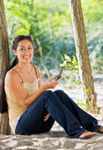 Woman text messaging on cell phone at beach — Stock Photo