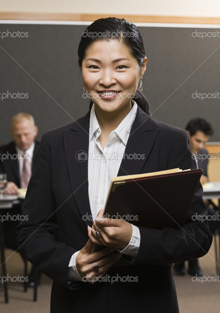 Businesswoman standing and smiling holding folder.  Vertically framed shot. — Stock Photo #18800597