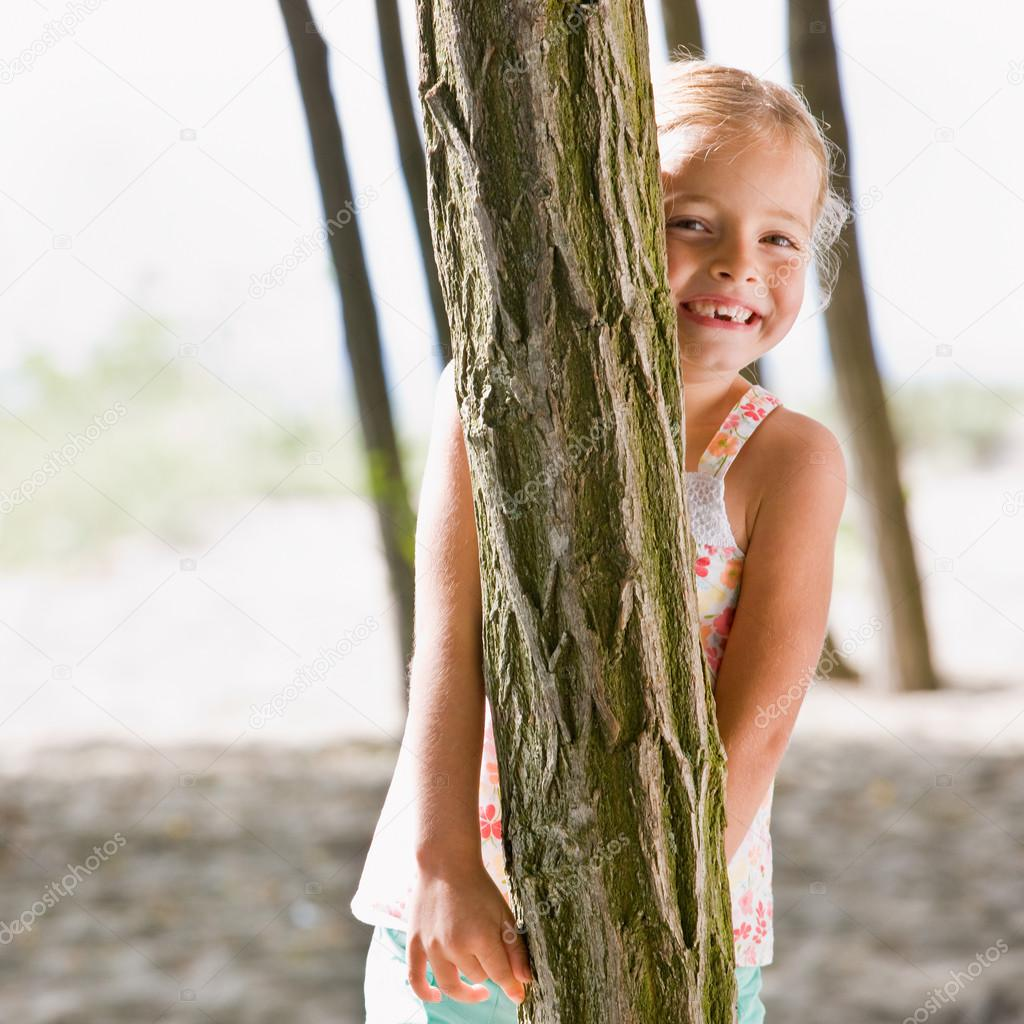 Girl hiding behind tree — Stock Photo #18803547