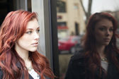 Young Woman with Beautiful Auburn Hair Reflected in a Window — Stock Photo