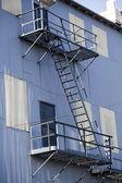 Construction en métal métal blanc et bleu avec l'escalier de secours — Photo