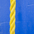 Yellow Rope on Blue Background - Stock Photo