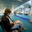 Woman Reading at an Empty Airport Lounge - Stock Photo