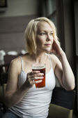 Blonde Woman with Beautiful Blue Eyes Drinking Glass of Pale Ale — Стоковое фото