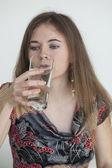 Mladá žena s krásné zelené oči pít sklenici vody — Stock fotografie