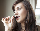 Beautiful Young Woman Eats Piece of Dark Chocolate — Stock Photo