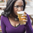 Stock Photo: Young AfricAmericWomDrinks Pint of Pale Ale