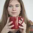 Young Woman with Beautiful Green Eyes with Red Coffee Cup — Stock Photo #22941842