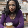 Angry Young African American Woman Drinks Pint of Pale Ale — Stock Photo #23264608