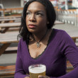 Thoughtful Young AfricAmericWomDrinks Pint of Pale Ale — Stock Photo #23265568