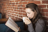 Young Woman with White Coffee Cup Reads Her Bible — Stock Photo