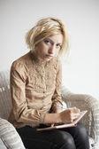 Loira jovem escrevendo no diário — Foto Stock
