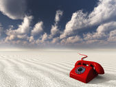 Red rotary phone in white landscape — Stock Photo