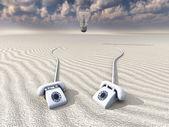White retro phones in desert with hovering bulb — Stock Photo