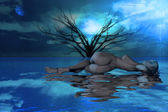 Woman lying on water near tree at night — Stock Photo