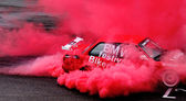 Red car in the red smoke — Stock Photo