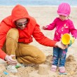 Father and his daughter playing on the beach — Stock Photo