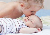 Little sister kissing baby brother — Stock Photo