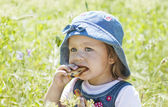 Cute baby eating crackers on green grass — Stock Photo