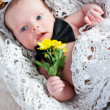 Cute newborn gentleman with flowers — Stock Photo