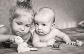 Cute little girl is playing with his younger brother — Stock Photo