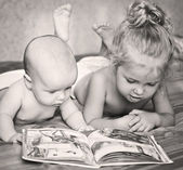 Little brother and sister looking at a book — Stock Photo
