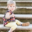 Little cute girl in sitting on the stairs with stone steps — Stock Photo #29508355