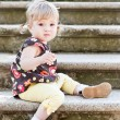 Little cute girl in sitting on the stairs with stone steps — Stock Photo