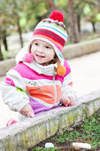 Happy toddler girl sitting with chalk — Stock Photo